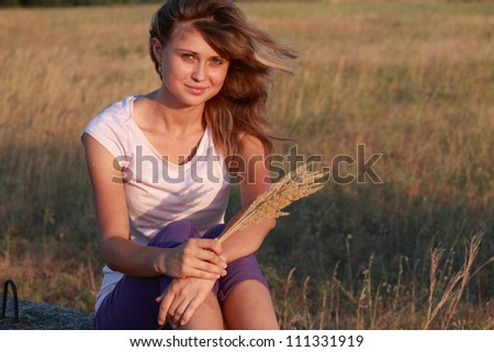 beautiful smiling girl with plants in the field