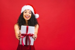 Beautiful smiling happy african american black woman in Santa Claus clothes isolated over red background. New year and christmas concept. Holding gift box.