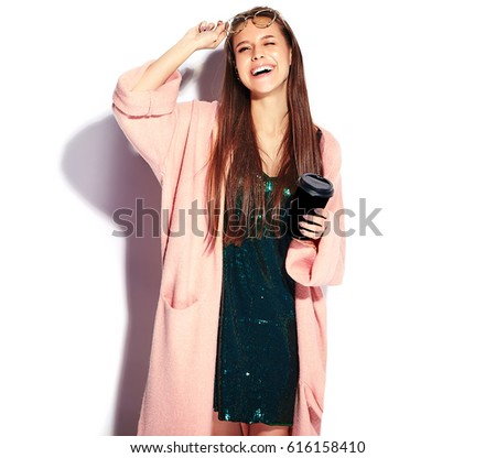 Beautiful smiling hipster brunette woman model in stylish pink overcoat and blue evening dress isolated on white background. Drinking coffee #616158410