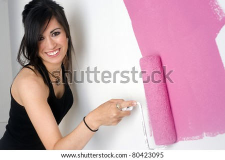 Beautiful Smiling Housewife Paints a Pink Stripe of Paint With Roller