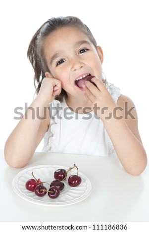Beautiful smiling little girl eating cherries over white