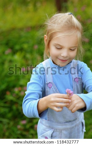 Beautiful smiling little girl in a denim suit holding flower.