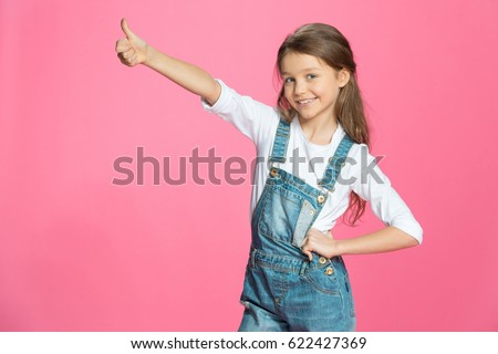 Beautiful smiling little girl in denim overalls showing thumb up on pink #622427369