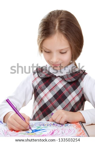 Beautiful smiling little girl sitting at table and draws felt-tip pen on paper, isolated on white background.