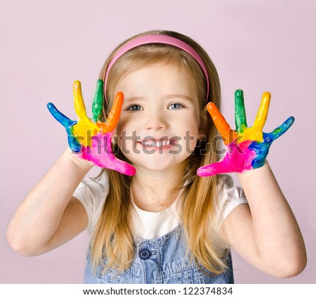 Beautiful smiling little girl with hands in the paint