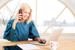Beautiful smiling mature businesswoman making call and using laptop while sitting at office desk. Home office.