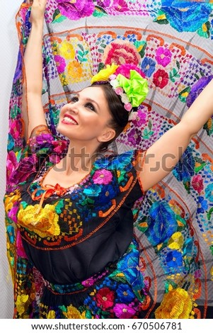 beautiful smiling mexican woman in traditional mexican dress hands up holding the skirt as a background like peacock #670506781