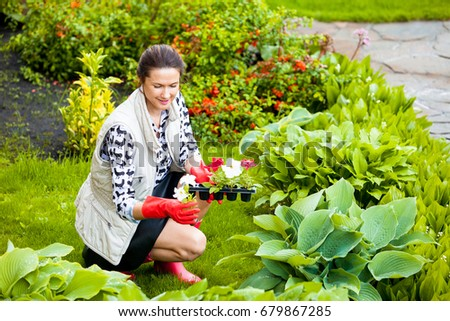 Beautiful smiling middle-aged woman in red rubber gloves planting flowers on the flower bed. Scene in the garden #679867285