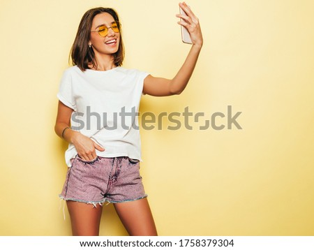 Beautiful smiling model dressed in summer hipster clothes.Sexy carefree girl posing in studio near yellow wall in jeans shorts.Trendy and funny woman taking selfie self portrait photos on smartphone