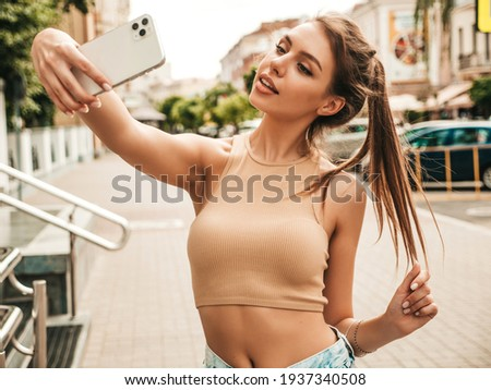 Beautiful smiling model in summer casual clothes.Sexy carefree female posing in the street in sunglasses.Taking selfie self portrait photos on smartphone