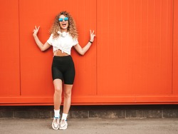 Beautiful smiling model with afro curls hairstyle dressed in summer hipster clothes.Sexy carefree girl posing in the street near red wall.Funny and positive woman having fun in sunglasses