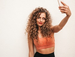 Beautiful smiling model with afro curls hairstyle dressed in summer hipster clothes.Sexy carefree female posing in the street near white wall.Funny and positive woman having fun. Makes selfie photos3