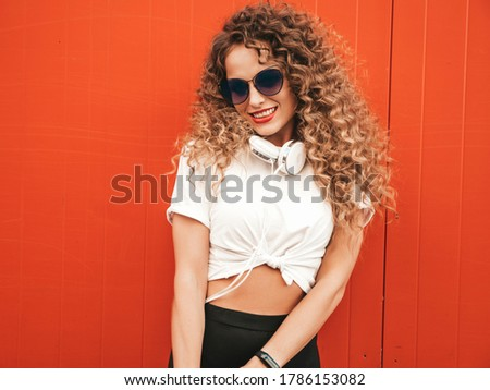 Beautiful smiling model with afro curls hairstyle dressed in summer hipster clothes.Sexy carefree girl posing near red wall outdoors.Funny and positive woman having fun in sunglasses