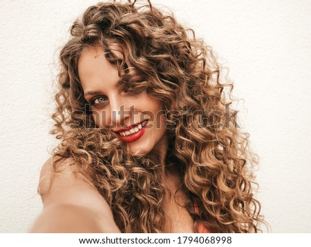Beautiful smiling model with afro curls hairstyle dressed in summer hipster clothes.Sexy carefree girl posing in the street near white wall.Funny and positive woman having fun. Makes selfie photos