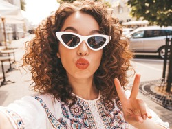 Beautiful smiling model with afro curls hairstyle dressed in summer hipster white dress.Sexy carefree girl posing in the street in sunglasses.Taking selfie self portrait photos on smartphone.Duck face