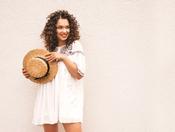 Beautiful smiling model with afro curls hairstyle dressed in summer hipster white dress.Sexy carefree girl posing in the street near white wall in hat.Funny, positive woman having fun and going crazy
