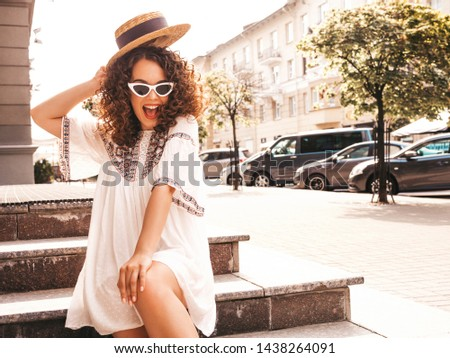 Beautiful smiling model with afro curls hairstyle dressed in summer hipster white dress.Sexy carefree girl posing in street.Trendy and positive woman having fun in sunglasses.In hat