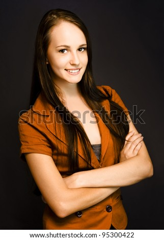 Beautiful smiling natural young girl holds a blank erased chalkboard to her chest ready for your text or message
