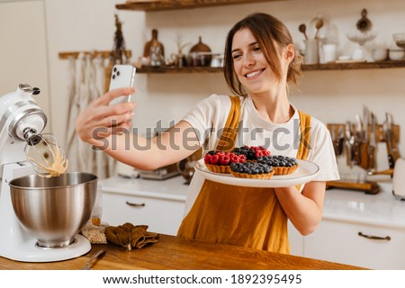 Beautiful smiling pastry chef woman taking selfie with tarts on cellphone at cozy kitchen