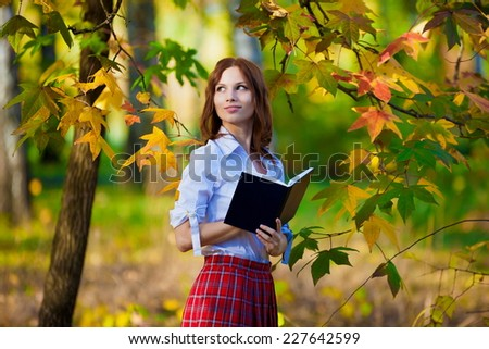 beautiful  smiling  schoolgirl in red skirt and white blouse posing in autumn nature has book