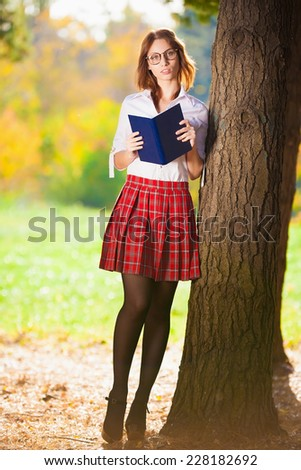beautiful  smiling  schoolgirl in red skirt and white blouse posing in autumn nature has book and glasses