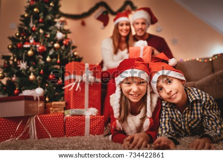 Beautiful smiling sister and brother enjoying at home in a Christmas time. They wear Santa hats and looking at camera. Selective focus. Focus on foreground, on children.