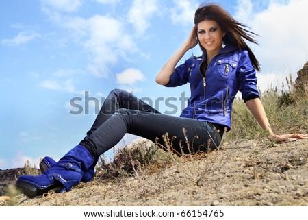 Beautiful smiling stylish girl on sky background