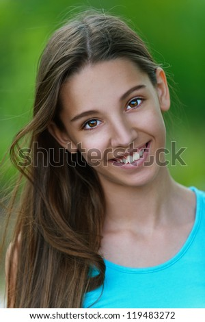 Beautiful smiling teenage girl, against green of summer park.