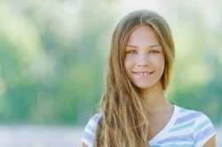 Beautiful smiling teenage girl in blue blouse, against green of summer park.