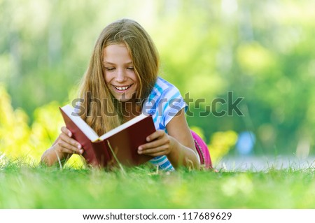 Beautiful smiling teenage girl in blue blouse lying on grass and read book, against green of summer park.