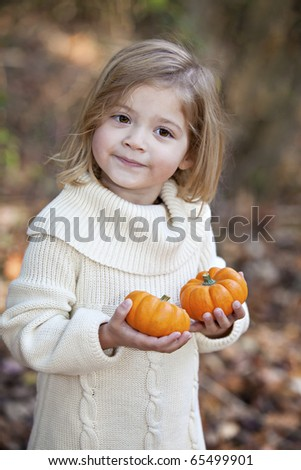 Beautiful smiling toddler outdoors holding little pumpkins and smiling with Autumn colors in background