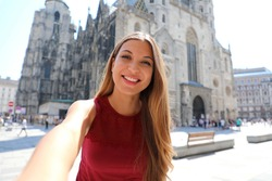 Beautiful smiling tourist girl taking self portrait with smartphone in Vienna with Saint Stephen's cathedral on the background in Austria, Europe