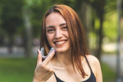 Beautiful smiling Turkish woman is holding an invisalign bracer with vibrant colors