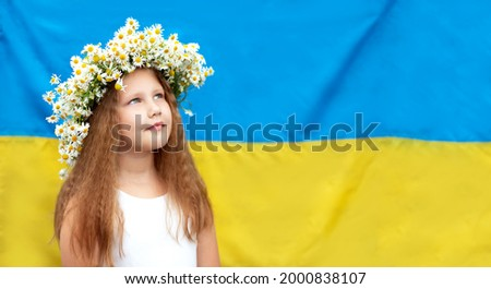 Beautiful smiling Ukrainian girl in a wreath of daisies against the background of the yellow-blue Ukrainian flag. Independence Day of Ukraine, Constitution Day, National Flag Day of Ukraine. 30 years  Photo stock ©