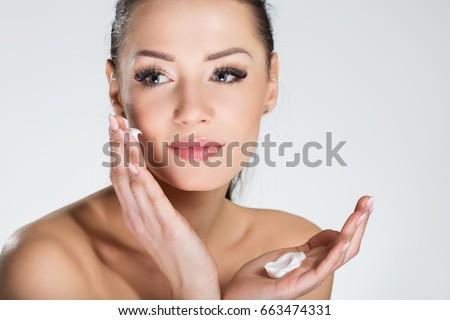 Beautiful smiling woman applying cream on face #663474331