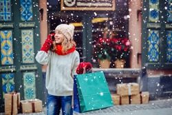 Beautiful  smiling woman at the street with shopping bags talking on mobile phone. Attractive girl  dressed in warm white  hat, red scarf and mittens. Magic snowfall effect.