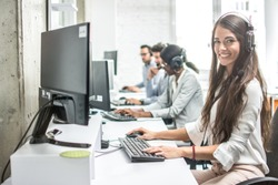 Beautiful smiling woman costumer support worker with headset using computer in call center.