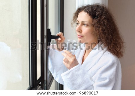 Beautiful smiling woman dressed in white bathrobe holds glass of water and opens window