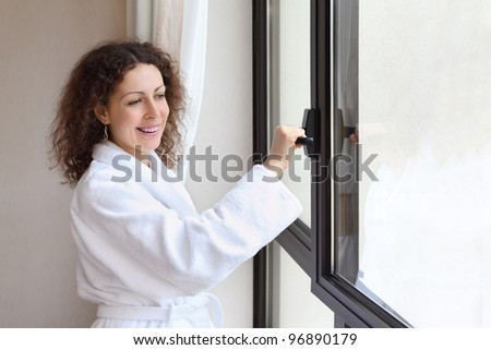 Beautiful smiling woman dressed in white bathrobe opens window