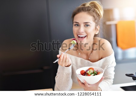 Beautiful Smiling Woman Eating Fresh Organic Vegetarian Salad In Modern Kitchen