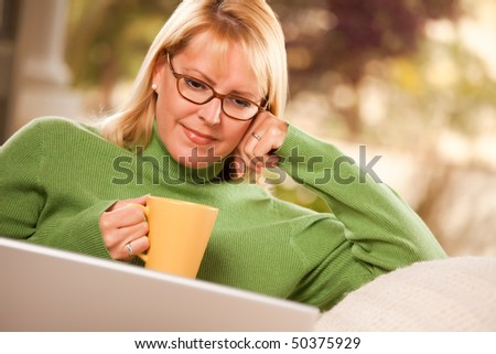 Beautiful, Smiling Woman Enjoys Her Warm Drink and Laptop Relaxing Day.