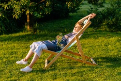 Beautiful smiling woman gardener in apron relaxing, stretching in a sun lounger on a grass meadow outdoor. She is absolutely happy. Slow living, gardening hobby concept