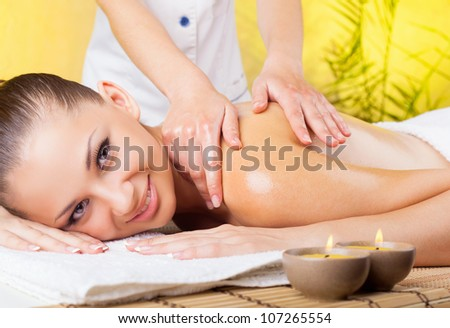 Beautiful smiling woman getting a massage in the spa salon
