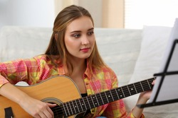 Beautiful smiling woman holding and playing western acoustic guitar portrait. Learning musical instrument, music shop or school, having fun enjoying hobby, live performance concept