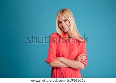 Beautiful smiling woman in red shirt standing with arms folded isolated on a blue background