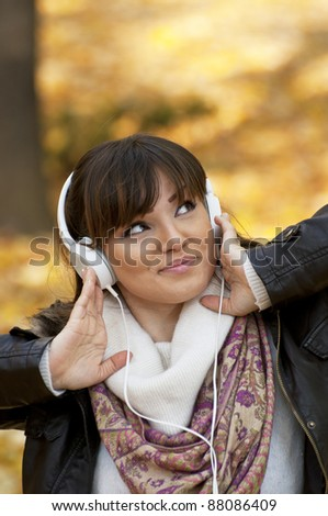 Beautiful smiling woman listening to music and dancing