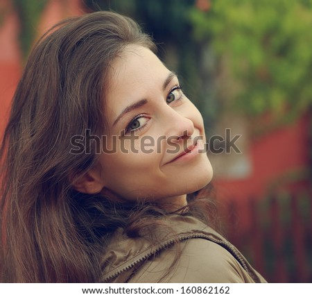 Beautiful smiling woman looking outdoors background. CLoseup portrait