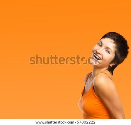 Beautiful smiling woman. Over orange background
