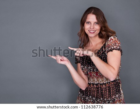 Beautiful smiling woman pointing with both hands to copyspace on her right hand side against a grey studio background