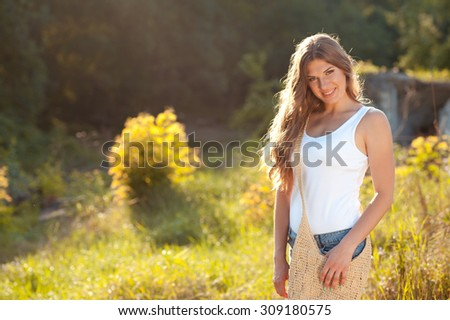 Beautiful smiling woman posing outdoors. Looking at camera. Wearing summer casual clothes. 20s.  Photo stock ©